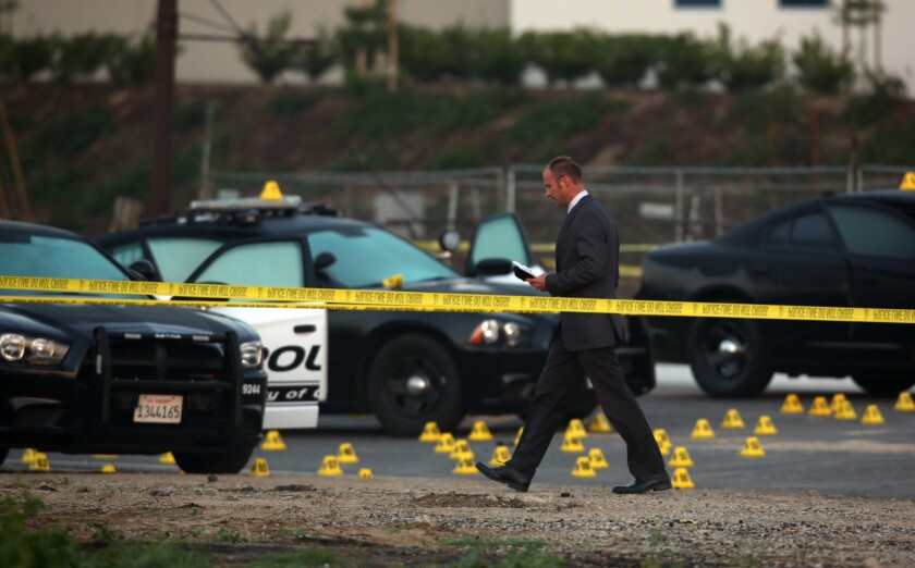 Evidence tags dot the area in Chino where a police chase ended with the fatal shooting of a man who was suspected of robbing a bank in Corona.