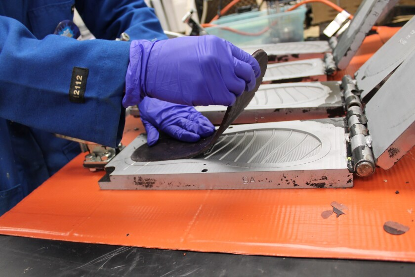 A flip-flop foot bed is pulled from a mold.