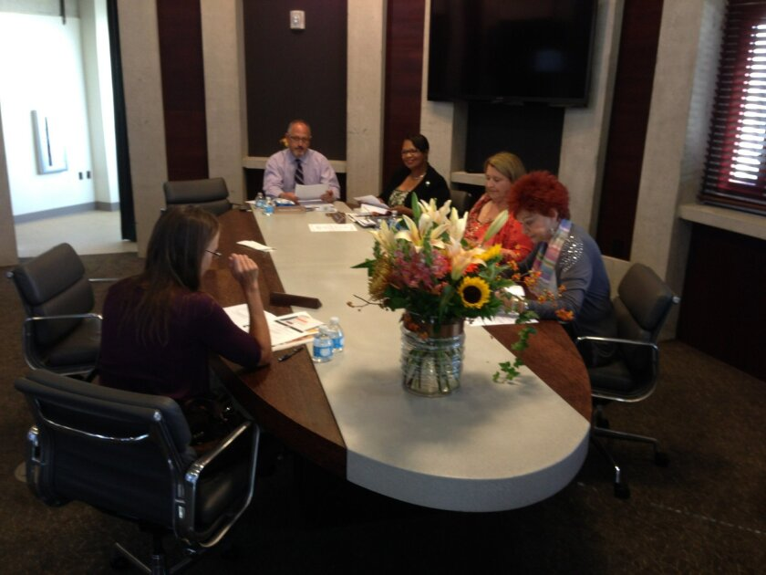 The Board of Library Commissioners holds its first meeting in the commission room on the top floor of the Central Library. At the head of the table is chairman Sal Giametta and to his left, librarian Deborah Barrow.
