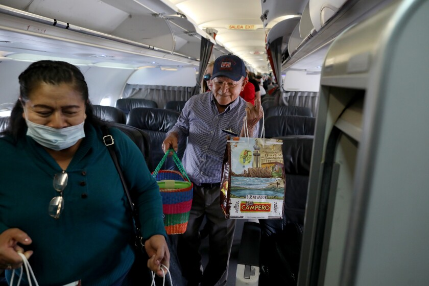 People carry bags of Pollo Campero fried chicken as they board a plane.