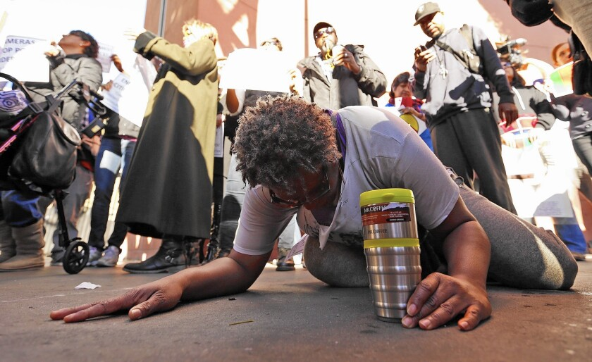 """Suzette Shaw, 50, screaming """"You can't kill,"""" lies down in protest at the skid row site where a homeless man was killed by LAPD officers."""