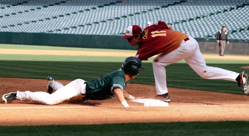 Costa Mesa High School player #21 Miguel Rodriguez slides in safe into third base as #11 Jake Covey