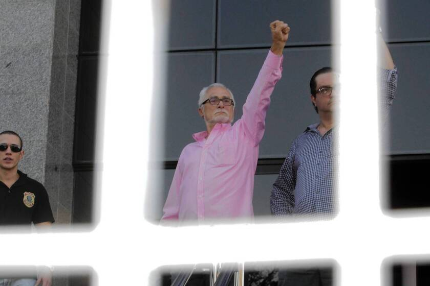 Jose Genoino, center, president of the Workers' Party during the time of the scandal, turns himself in to federal police supervision in Sao Paulo, Brazil, this month.