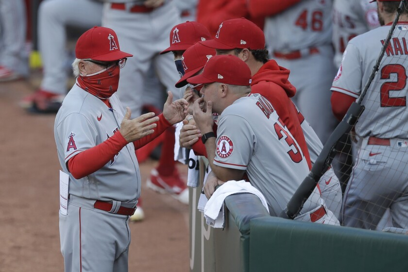 Angels manager Joe Maddon, left, talks with his team before its game against the Athletics on July 24, 2020.