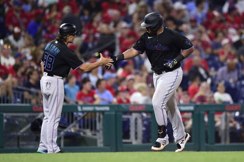 Miami Marlins' Jesus Aguilar, right, is congratulated by third base coach Trey Hillman after Aguilar hit a three-run home run off Philadelphia Phillies Enyel De Los Santos during the fourth inning of the second baseball game of a doubleheader, Friday, July 16, 2021, in Philadelphia. (AP Photo/Derik Hamilton)