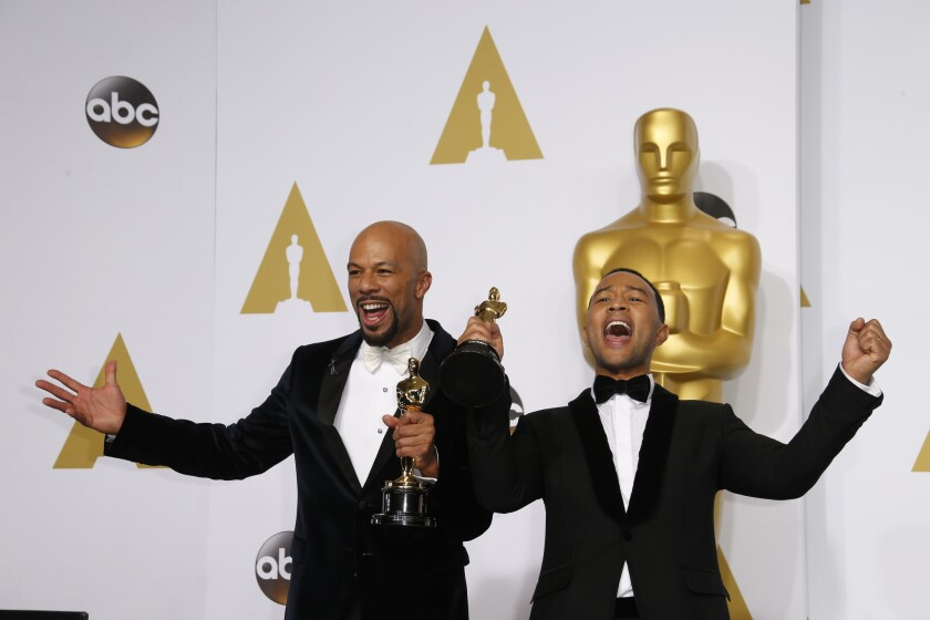 """Rapper Common (left) and John Legend hold their Oscars at the 2015 Academy Awards after winning Best Song honors for """"Glory,"""" which they co-wrote for the film """"Selma."""""""
