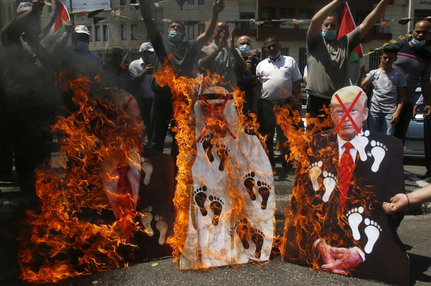 """FILE - In this Aug. 14, 2020 file photo, Palestinians burn pictures of U.S. President Donald Trump, Abu Dhabi Crown Prince Mohammed bin Zayed al-Nahyan and and Israeli Prime Minister Benjamin Netanyahu during a protest against the United Arab Emirates' deal with Israel, in the West Bank city of Nablus. For the first time in more than a quarter-century, a U.S. president will host a signing ceremony, Tuesday, Aug. 15, between Israelis and Arabs at the White House, billing it as an """"historic breakthrough"""" in a region long known for its stubborn conflicts. .(AP Photo/Majdi Mohammed, File)"""
