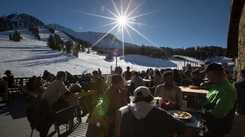 Skiers and snowboarders enjoy food and beverages at Tusks Bar overlooking the slopes at Mammoth Mountain. The resort and others owned by Mammoth Resorts are being bought by a Colorado partnership.