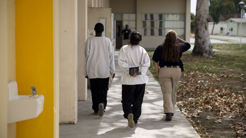 An officer escorts young women detained at Los Padrinos Juvenile Hall in Downey in 2016. Six detention officers have been charged with felonies and misdemeanors in connection with their use of pepper spray.