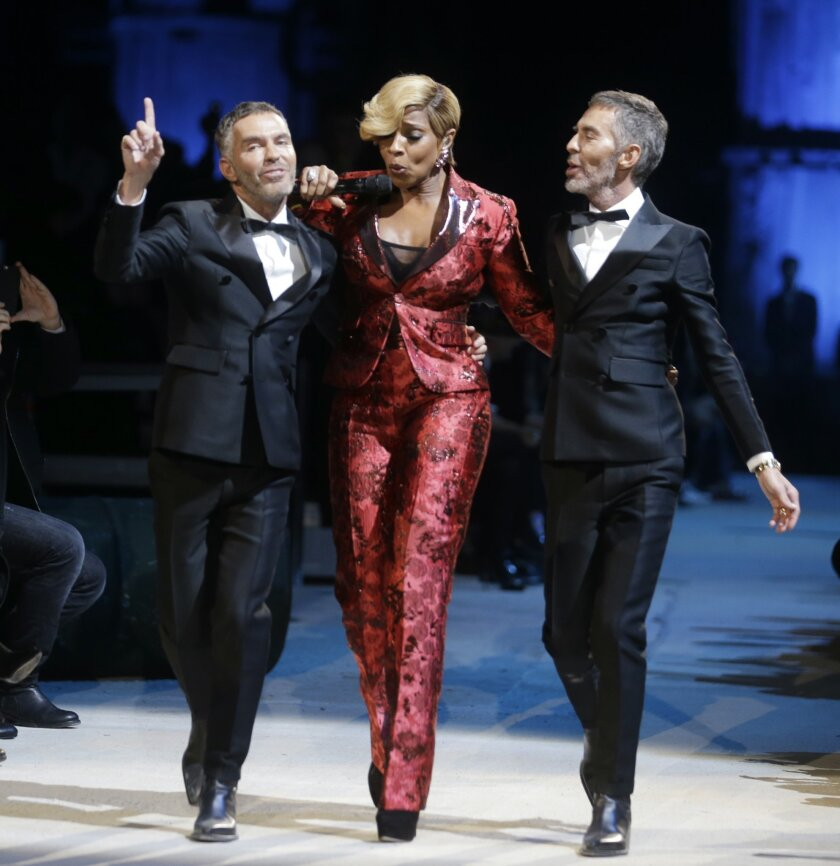 US singer Mary J. Blige, center, performs as Canadian fashion designers Dean Caten, left and Dan Caten acknowledge the applause of the audience after presenting their DSquared2 men's Fall-Winter 2015-2016 collection, part of the Milan Fashion Week, unveiled in Milan, Italy, Friday, Jan. 16, 2015. (