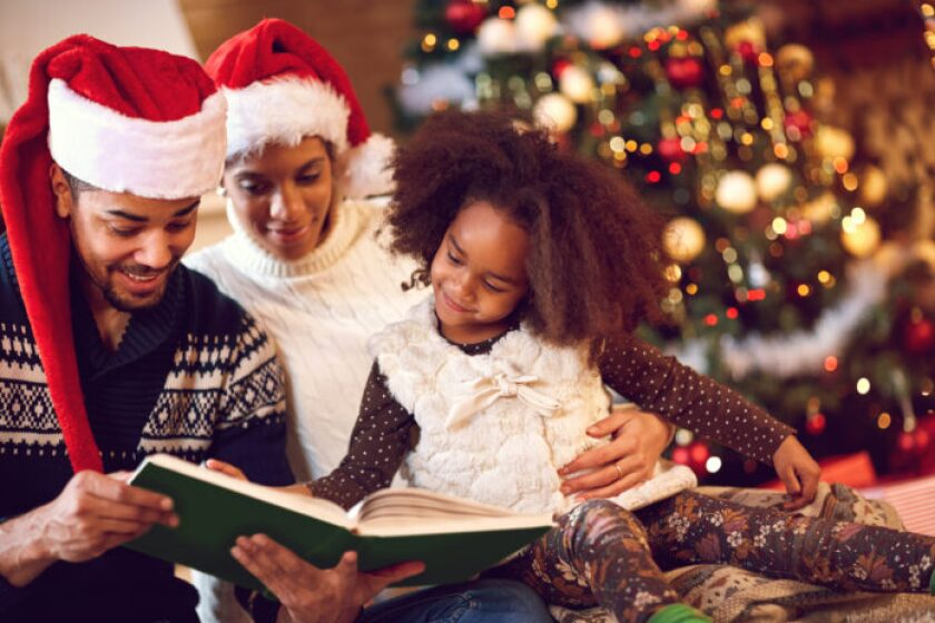 smiling mother, father and daughter read a book at fireplace on Christmas