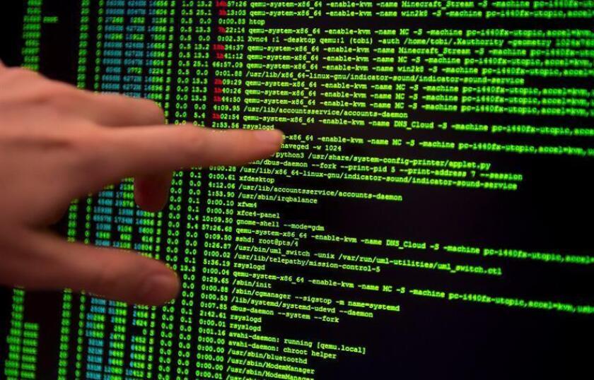 Fotografía de una computadora HP, señalando al código en la pantalla. EPA/Archivo