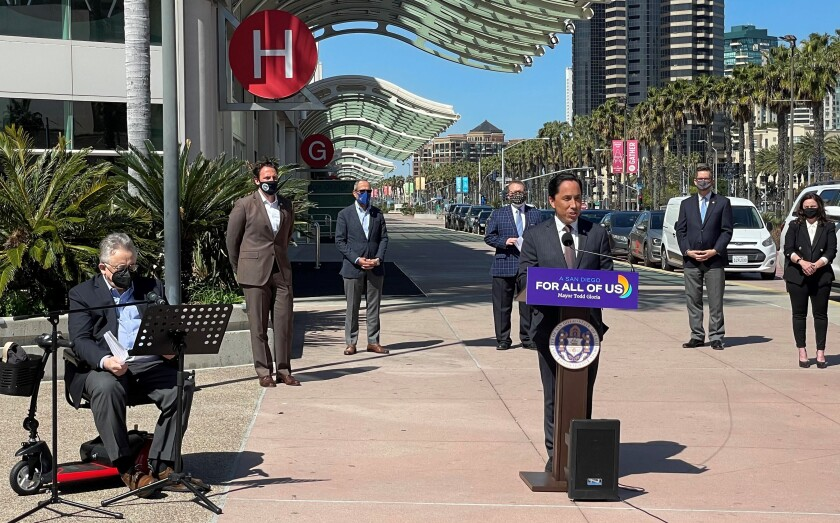 San Diego Mayor Todd Gloria speaks at a lectern outside the San Diego Convention Center.