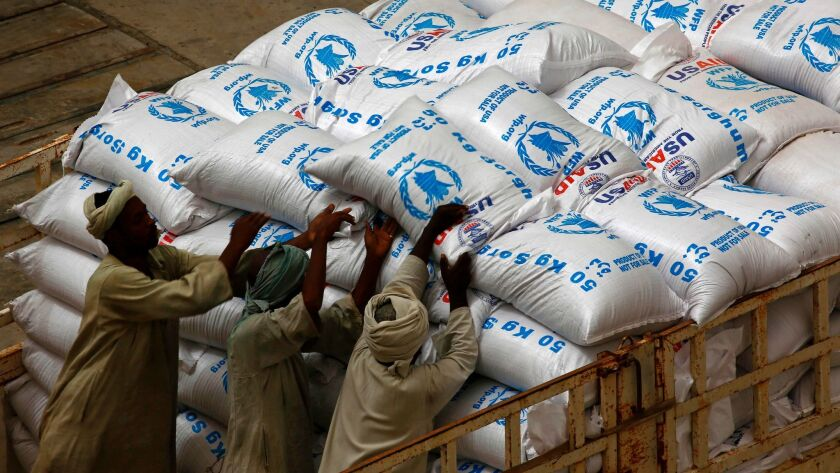 Sudanese workers unload U.S. aid destined for South Sudan from the World Food Program at Port Sudan in March 2017.