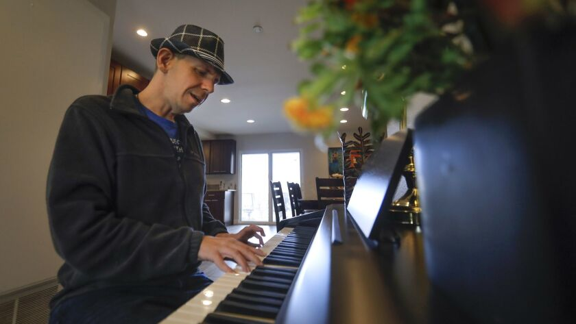 Chris Baker, 32, who is on the autism spectrum, sings and plays piano at the TERI Inc. group home in La Costa that he shares with five other adults with developmental disabilities.