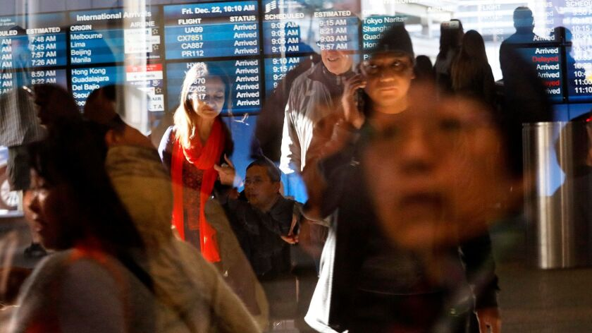 Travelers, reflected in sliding glass doors, take part in the Christmas getaway at the Tom Bradley International Terminal at Los Angeles International Airport on Dec. 22, 2017.