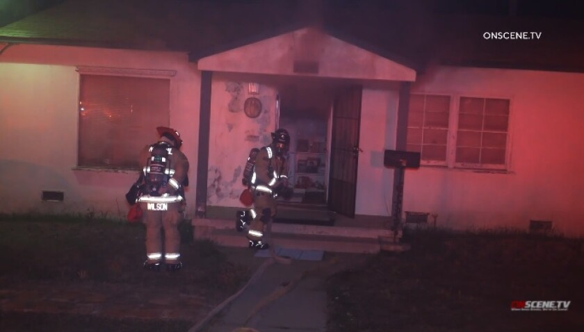 Firefighters work to extinguish a house fire Wednesday night in National City as smoke drifts from the home.