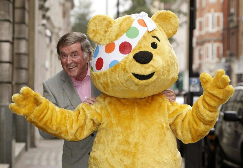 """FILE - In this Nov. 6, 2008 file photo, Terry Wogan poses with Pudsey Bear, the mascot of the charity Children in Need in London. Wogan, one of the best-known voices and faces on British television and radio, has died aged 77. His family said in a statement Wogan died Sunday, Jan. 31, 2016 surrounded by family members """"after a short but brave battle with cancer."""" (Yui Mok/PA via AP, File) UNITED KINGDOM OUT"""
