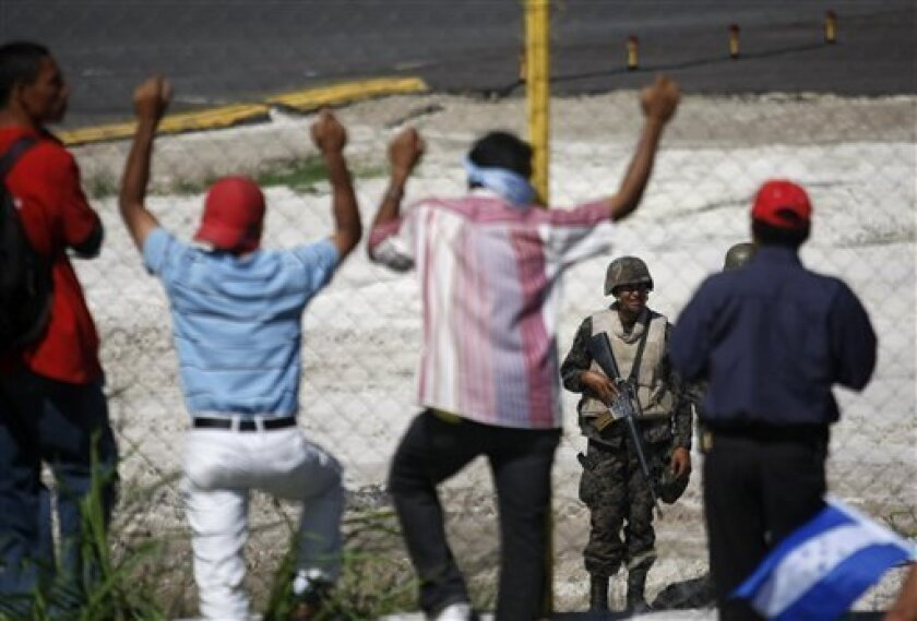 Supporters of ousted Honduras' President Manuel Zelaya stand next to the fence protecting the airfield as soldiers guard the international airport on the other side in Tegucigalpa, Saturday, July 4, 2009. Zelaya announced Saturday that he would return to Honduras to try to retake office following last week's military-backed coup, despite the interim government's insistence that he faces arrest and trial. (AP Photo/Dario Lopez-Mills)