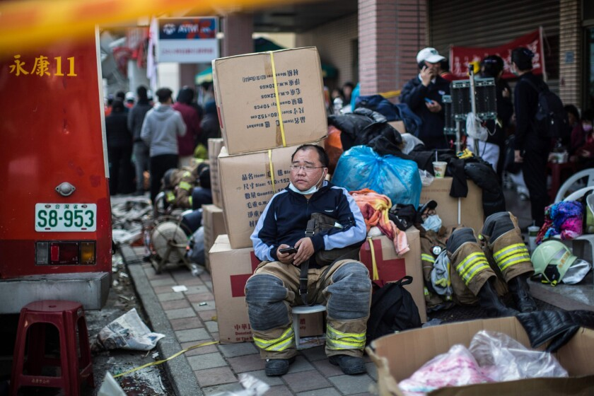 A firefighter rests near a collapsed building in the southern Taiwan city of Tainan.
