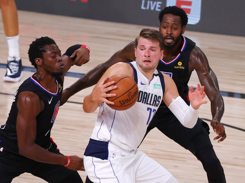 Dallas Mavericks' Luka Doncic is pressured by Clippers' Reggie Jackson and JaMychal Green.