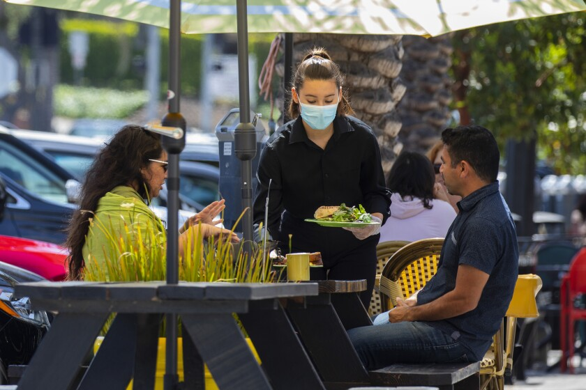 A masked server delivers food to diners at an outdoor restaurant