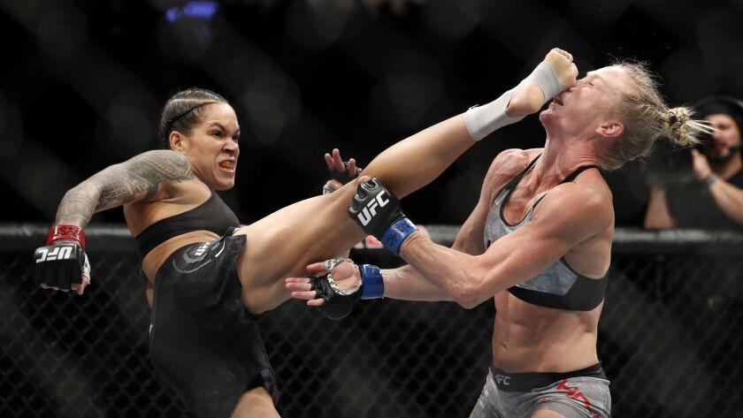 Amanda Nunes of Brazil lands a kick on Holly Holms that knocked her to the mat in the first round of