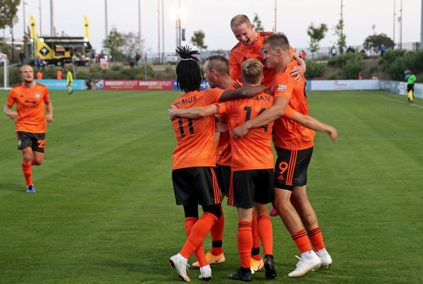 Orange County Soccer Club players celebrate a goal by midfielder Chris Wehan, bottom second from right, in the home opener.