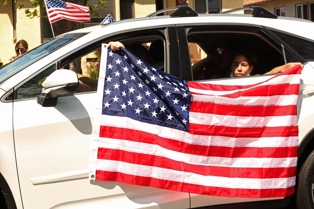 A driver and passenger hold the U.S. flag while joining a parade to honor World War II veteran Lt. Col. Sam Sachs in Lakewood on April 26.