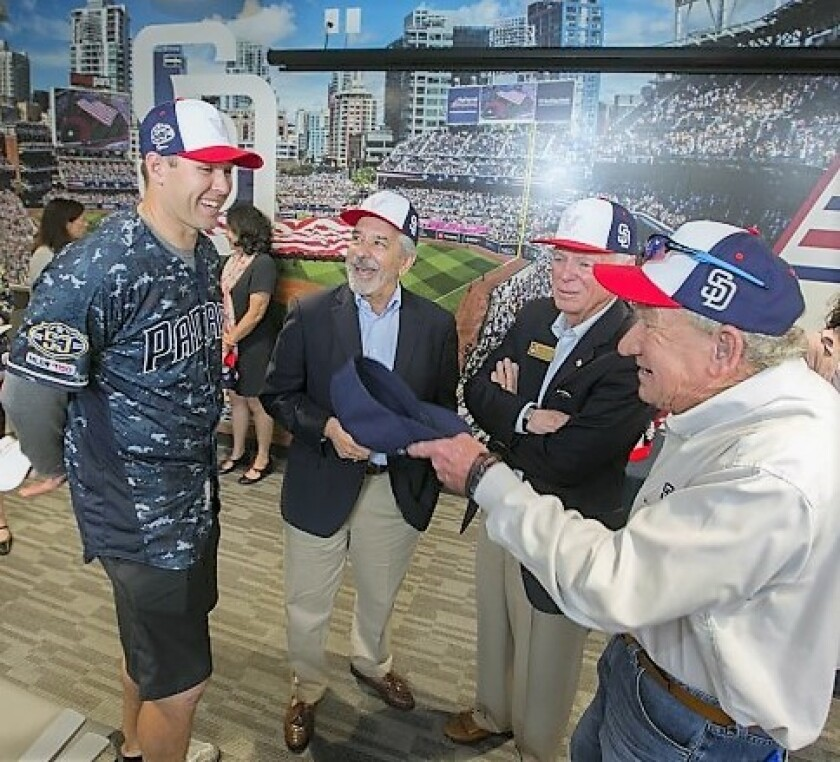 The San Diego Padres donated a new Padres Community Room at the Veterans Village of San Diego (VVSD) Steven A. Cohen Military Family Clinic in Mission Valley on June 17. (From left) Padres pitcher Craig Stammen, VVSD board member Tom Topuzes and Vice Chairman Mike Madigan talk with former Padres pitcher Randy Jones in front of the centerpiece mural after the dedication ceremony.