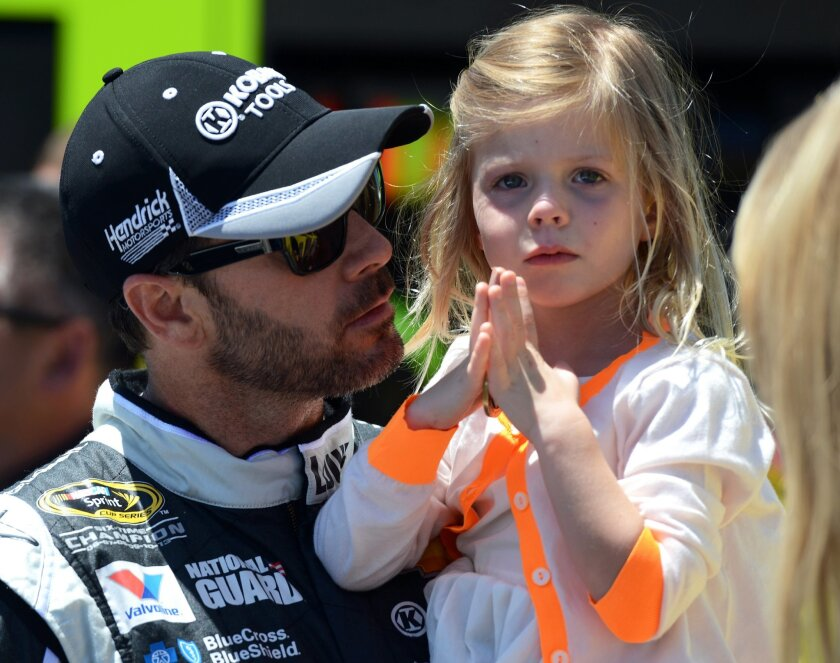 Driver Jimmie Johnson holds his daughter Genevieve, right, before driving in the NASCAR Sprint Cup series auto race at Dover International Speedway, Sunday, June 1, 2014, in Dover, Del. (AP Photo/Molly Riley)