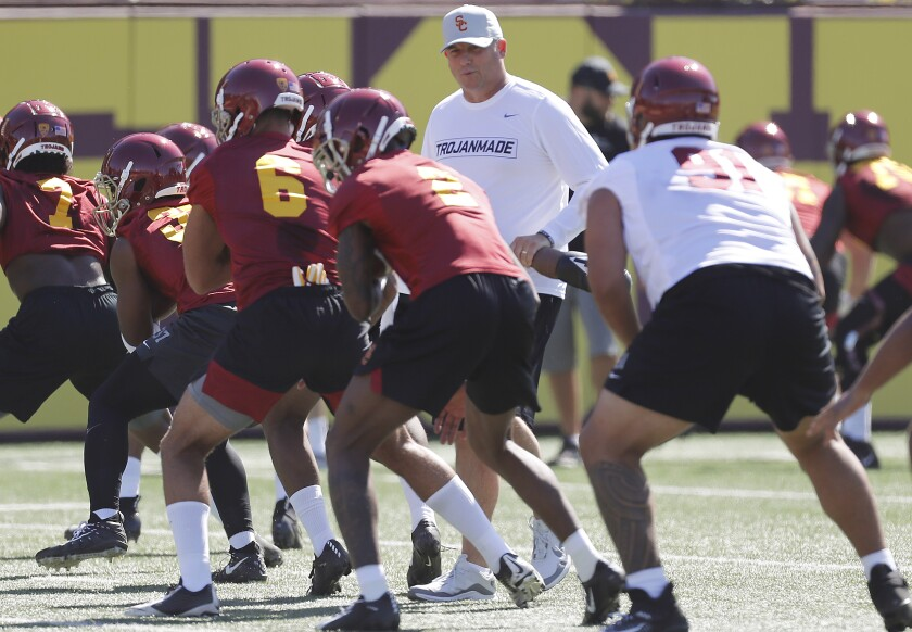 USC head football coach Clay Helton runs players through warm-ups during the opening of training camp at USC on Aug. 2.