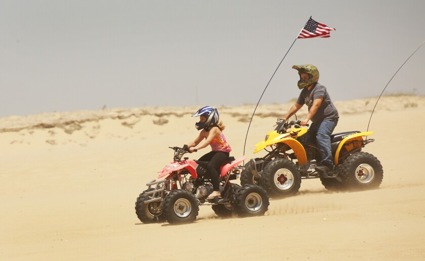 A girl and boy ride all-terain vehicles on a sand dune at Oceano Dunes