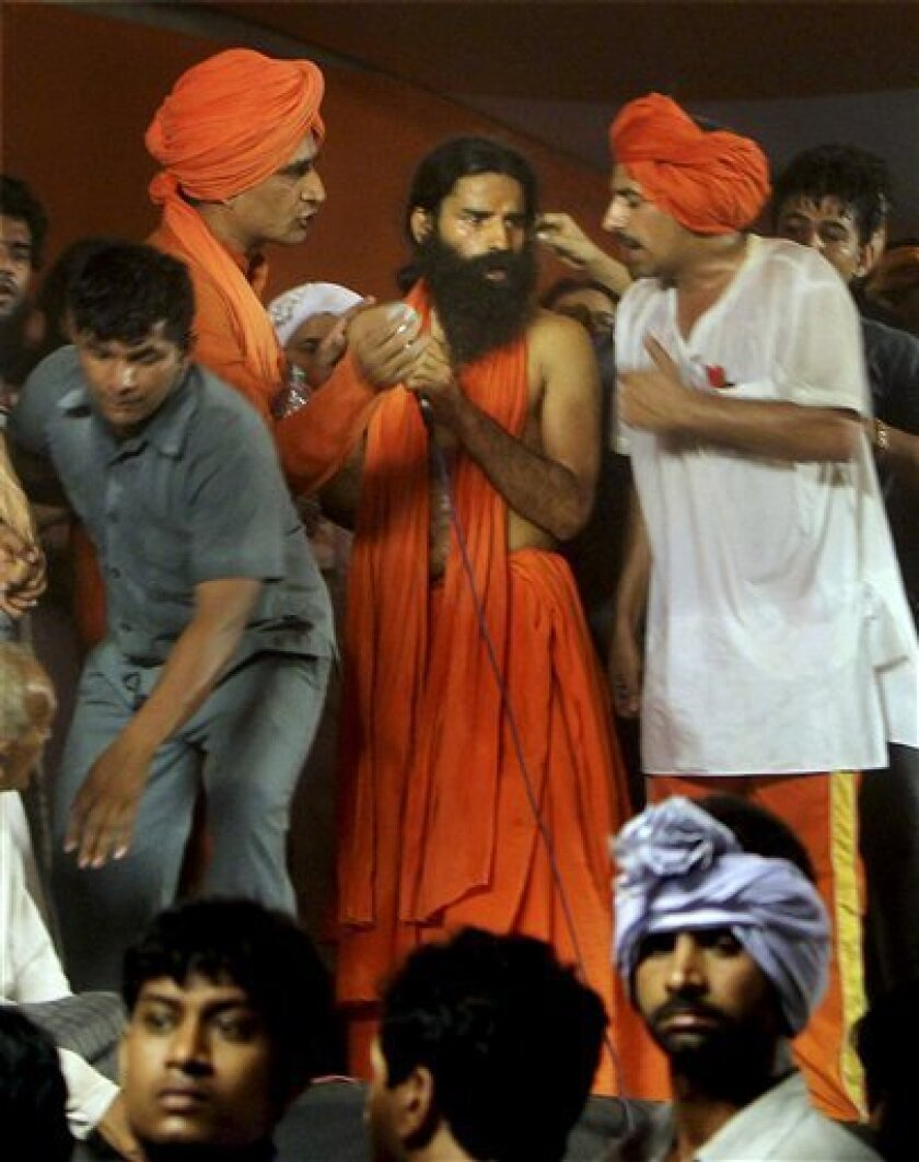 Renowned yoga guru Baba Ramdev, in orange, and supporters gather after clashing with police and shortly before his detention during their hunger strike in New Delhi, early Sunday, June 5, 2011. Police officers swooped down Sunday on the venue of the hunger strike by the charismatic Indian yoga guru and forcibly removed him and thousands of his supporters. (AP Photo) INDIA OUT