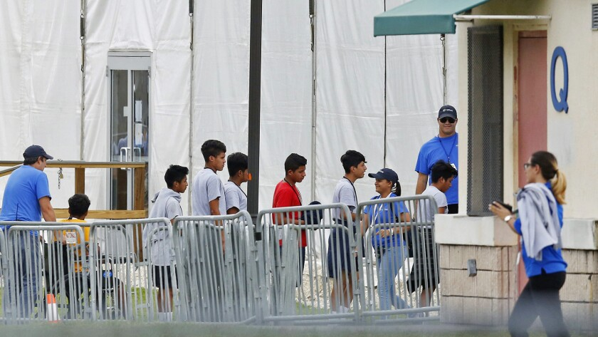 FILE - In this June 20, 2018, file photo, Immigrant children walk in a line outside the Homestead Te