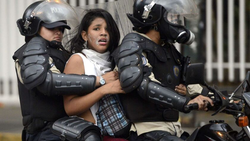 An anti-government activist is arrested and taken away by national police during a protest against Venezuelan President Nicolas Maduro in 2014