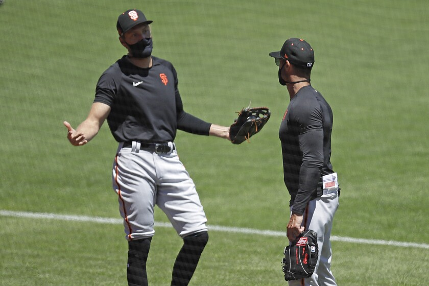San Francisco Giants' Hunter Pence, left, gestures while speaking with manager Gabe Kapler during a baseball practice Friday, July 10, 2020, in San Francisco. (AP Photo/Ben Margot)