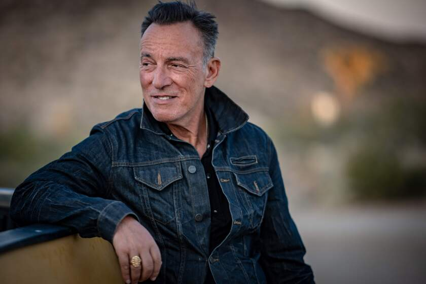 Bruce Springsteen stands in the outdoors in a denim jacket.