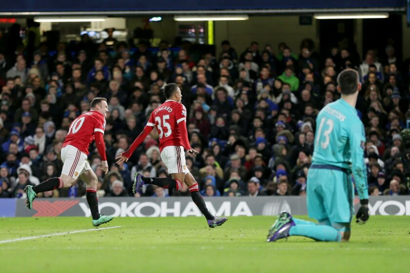 Manchester United's Jesse Lingard, center, celebrates with captain Wayne Rooney after scoring his side's first goal watched by Chelsea's goalkeeper Thibaut Courtois, right, during the English Premier League soccer match between Chelsea and Manchester United at Stamford Bridge stadium in London, Sun