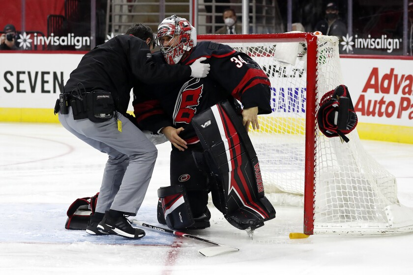 Carolina Hurricanes goaltender Petr Mrazek (34) is helped up by a team trainer after an injury during the first period of the team's NHL hockey game against the Dallas Stars in Raleigh, N.C., Saturday, Jan. 30, 2021. (AP Photo/Karl B DeBlaker)