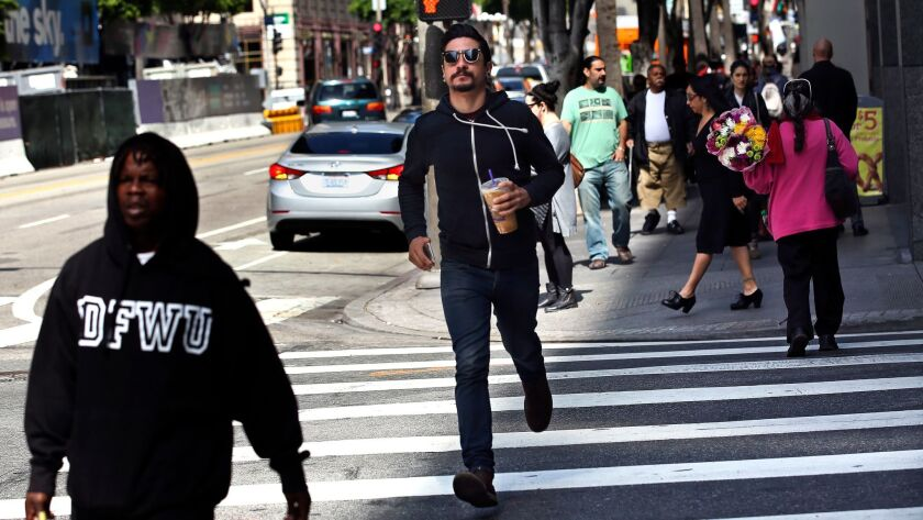 A pedestrian runs across the crosswalk at the intersection of Hope St. and 7th St. in Downtown Los Angeles on April 10, 2015.
