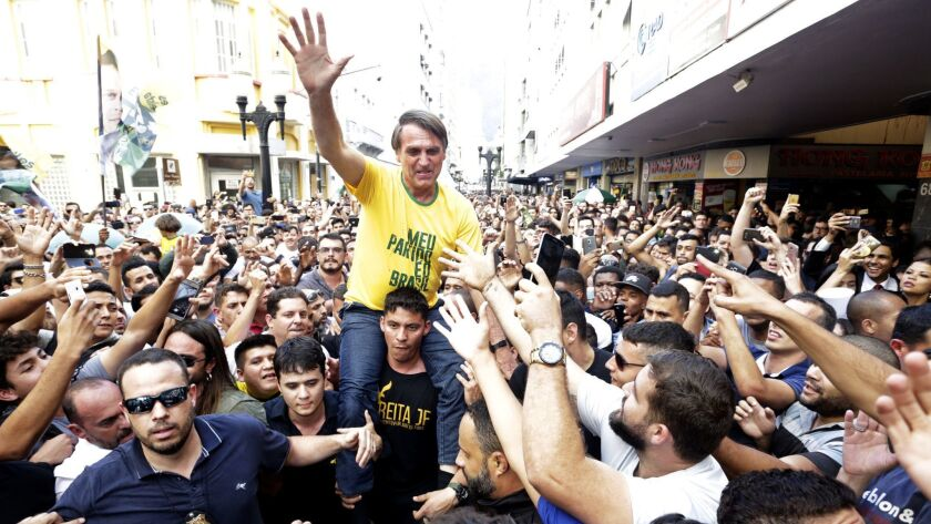 Presidential candidate Jair Bolsonaro is taken on the shoulders of a supporter moments before being