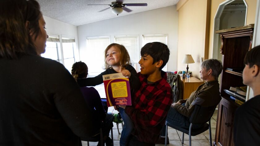 LOS MOLINOS, CA - NOVEMBER 24, 2018: Paradise Camp fire evacuees Gage Smith hands off his sister Wil