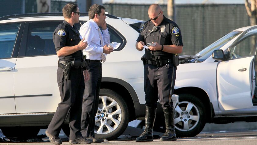 NEWPORT BEACH, CA, August 22, 2013 -- The driver, center, of a white BMW SUV is questioned by member
