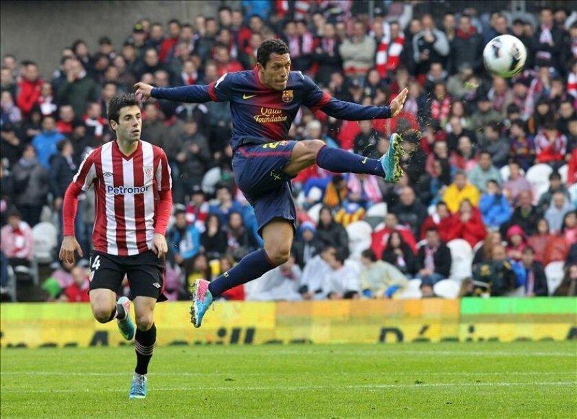 El defensa del FC Barcelona Adriano(d) despeja un balón ante la mirada del delantero del Athletic Club de Bilbao Markel Susaeta. EFE/Archivo