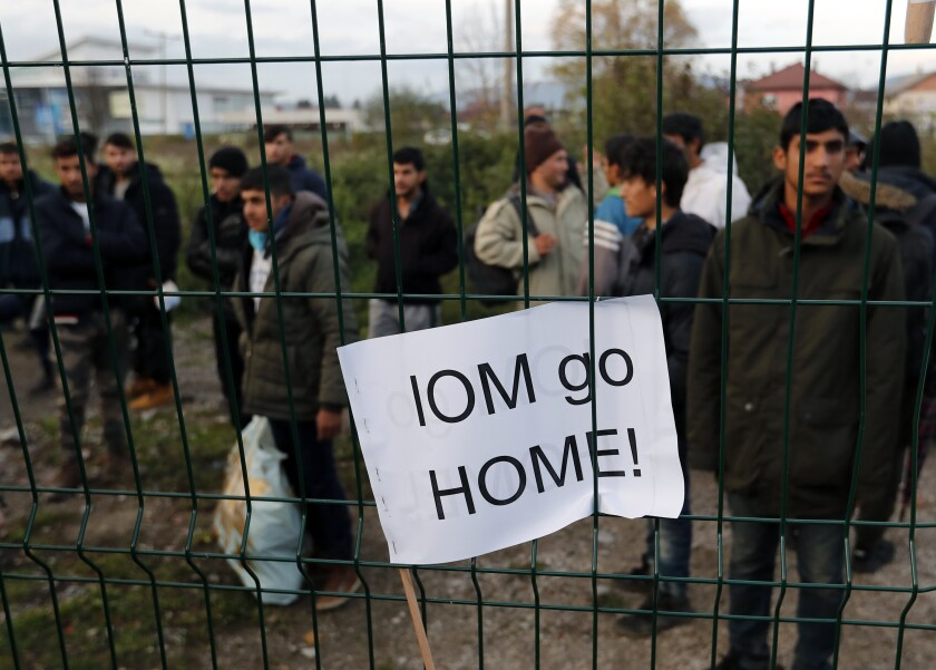 "Migrants at the Bira refugee camp in Bihac, northwest Bosnia, watch protesters demanding their relocation and the closure of overcrowded camps. A banner stuck in the fence reads ""IOM go home!"" referring to the International Organization for Migration."