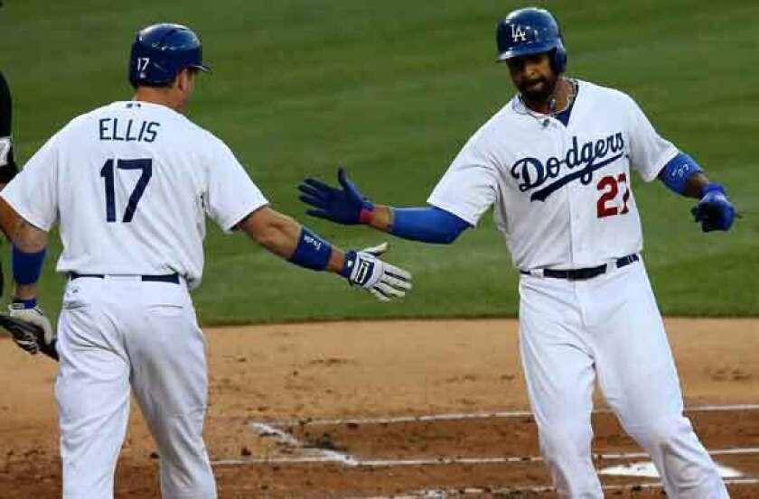 Dodgers catcher A.J. Ellis congratulates center fielder Matt Kemp after he scores in the first inning Wednesday night.
