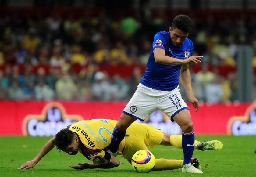 El jugador de América Oribe Peralta (i) disputa un balón ante Ángel Mena (d) del Cruz Azul durante el juego correspondiente a la jornada 13 del torneo mexicano de fútbol celebrado en el estadio Azteca, en Ciudad de México (México). EFE/Archivo