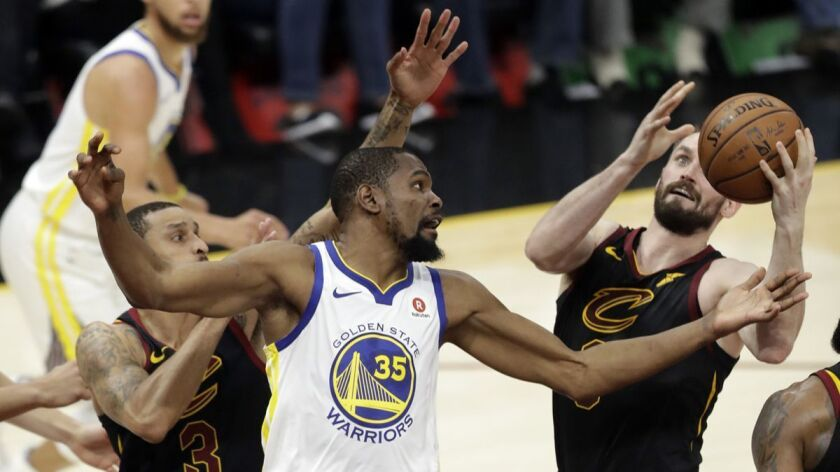Golden State Warriors' Kevin Durant (35) and Cleveland Cavaliers' Kevin Love, right, vie for a loose