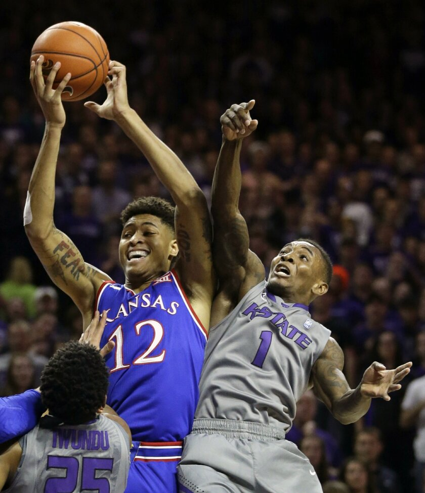 Kansas guard Kelly Oubre Jr. (12) rebounds against Kansas State guard Jevon Thomas (1) during the first half of an NCAA college basketball game in Manhattan, Kan., Monday, Feb. 23, 2015. (AP Photo/Orlin Wagner)